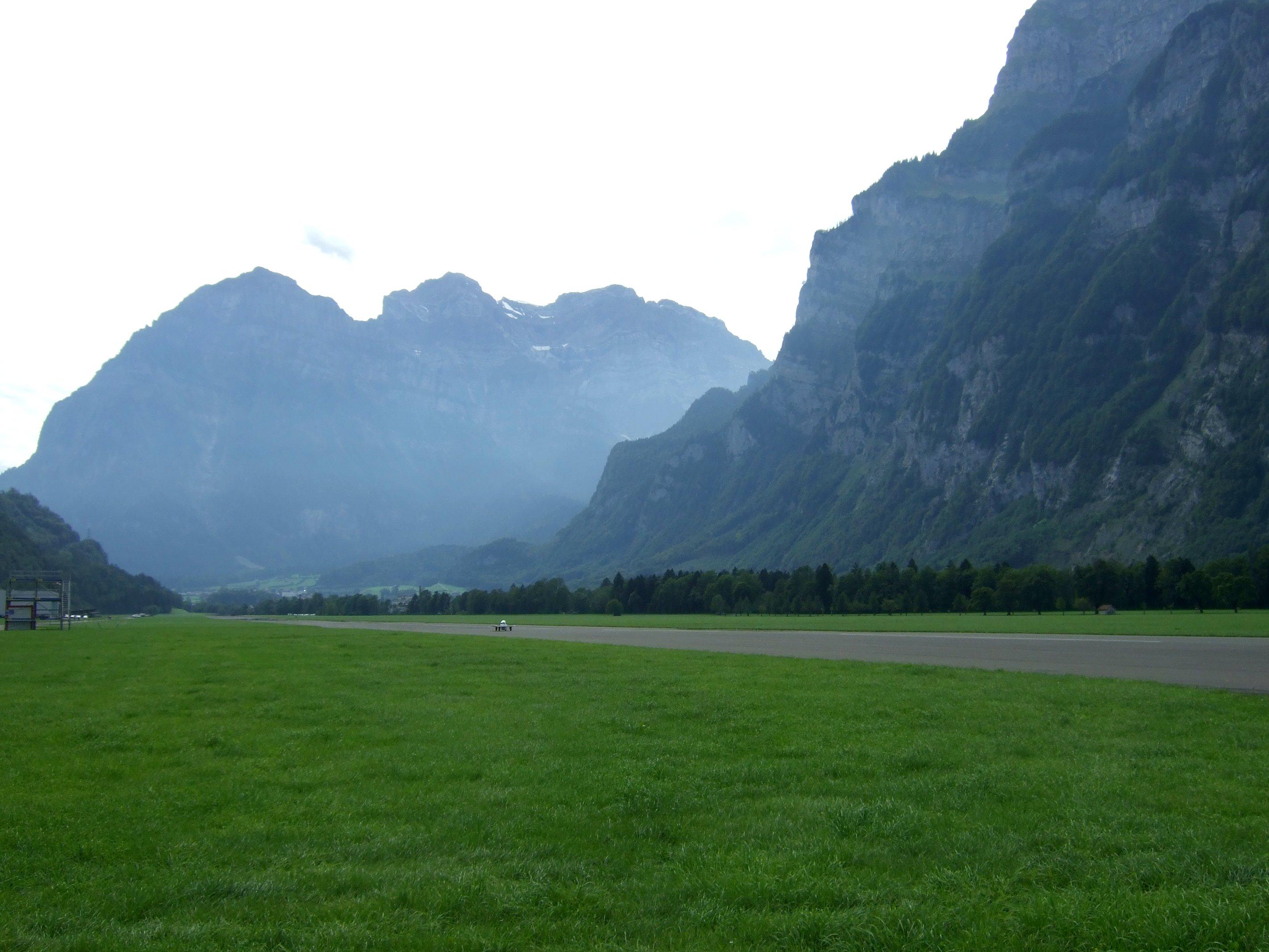 Kleines Auto auf grosser Fahrt und langer Piste neben hohen Bergen.