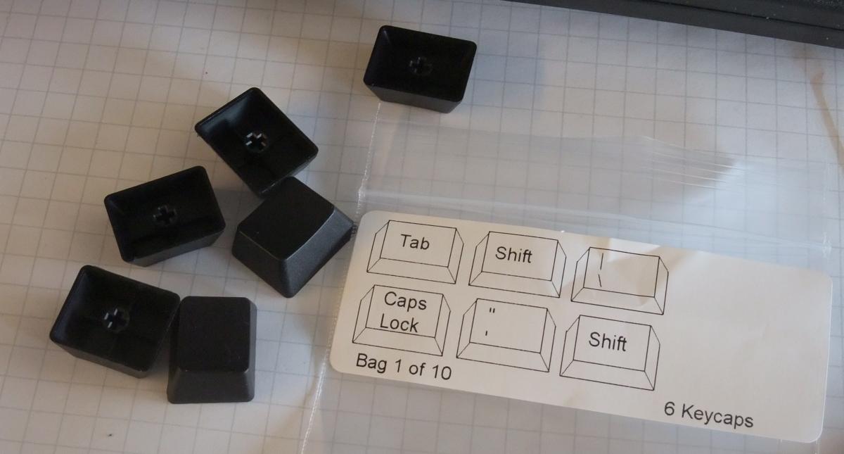 Schwarze Tastenkappen, in Tüten verteilt. Wie LEGO.
