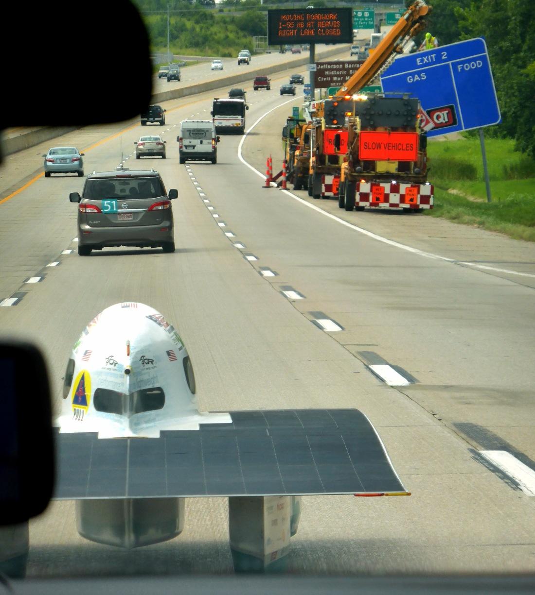 Kleines Auto auf grosser Fahrt auf dem Highway.