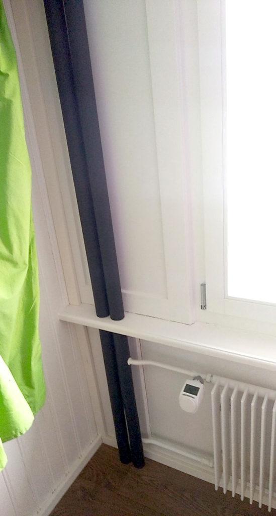Isolierte Rohre im Gästezimmer hinterm Vorhang.